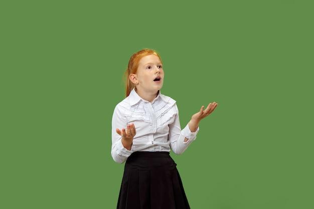 Красивая девочка-подросток выглядит удивленно изолированной на зеленом