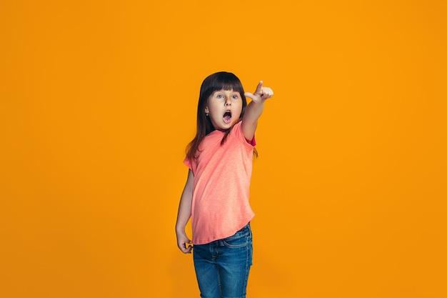 オレンジ色に分離されて驚いて見ている美しい十代の少女