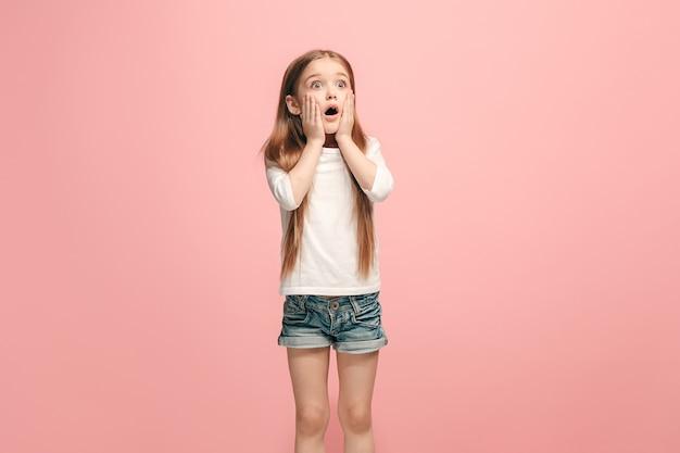 Красивая девочка-подросток выглядит удивленной, изолированной на розовом