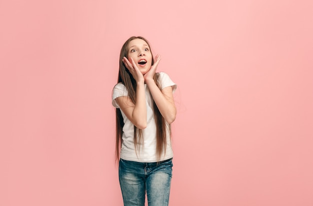 ピンクで隔離されて驚いて見える美しい十代の少女