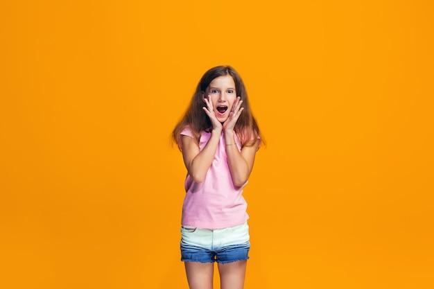 Beautiful teen girl looking suprised isolated on orange