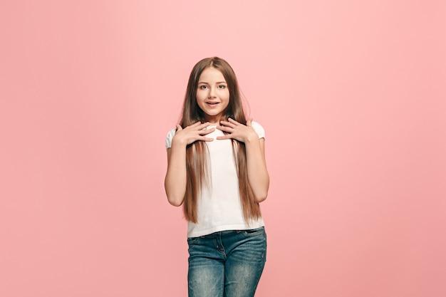 ピンクの壁に孤立して驚いて見える美しい十代の少女
