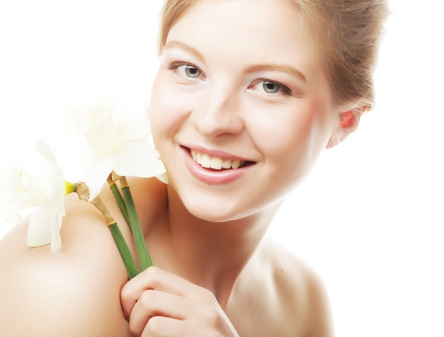 Красивая девочка-подросток улыбается и с цветком нарцисса и смотрит в камеру.