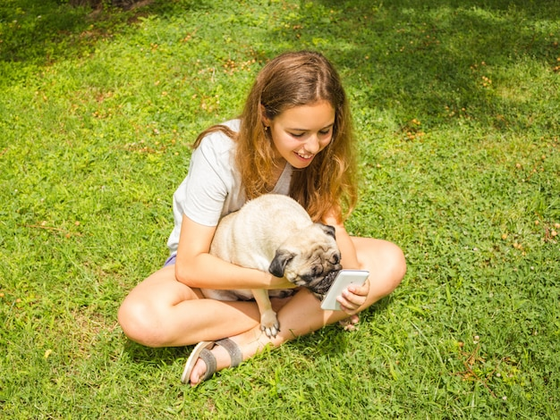 Beautiful teen girl watching a funny video on a smartphone with her dog in a summer park