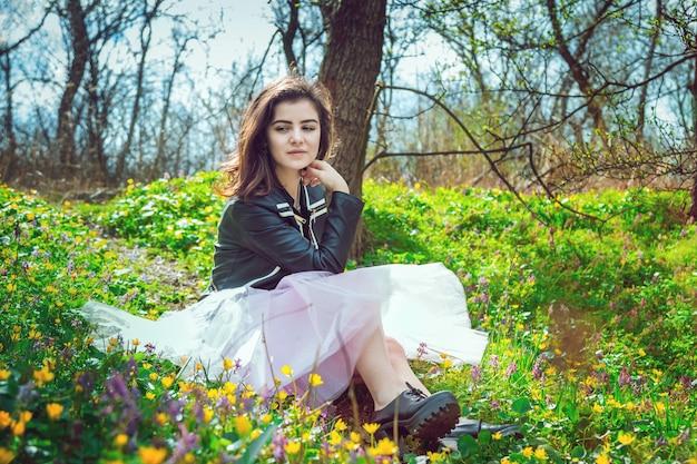 Красивая девушка в черной кожаной куртке и розовой юбке из тюля-пачки сидит на весеннем лугу с желтыми и фиолетовыми цветами в лесу