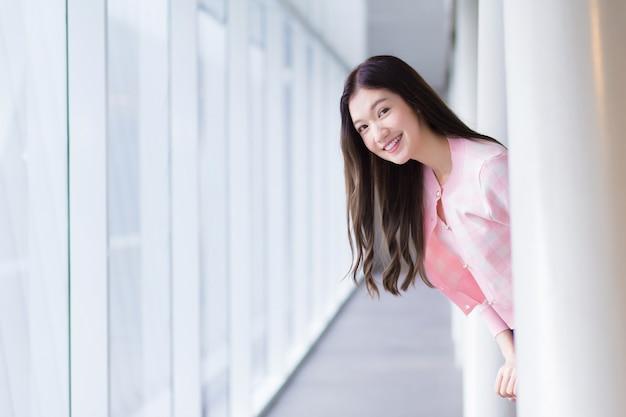 美しい10代のアジアの女の子は、ピンクのシャツを着た白を着て、天気の良い日にガラス張りの窓の近くに立っている間、元気に笑っています。