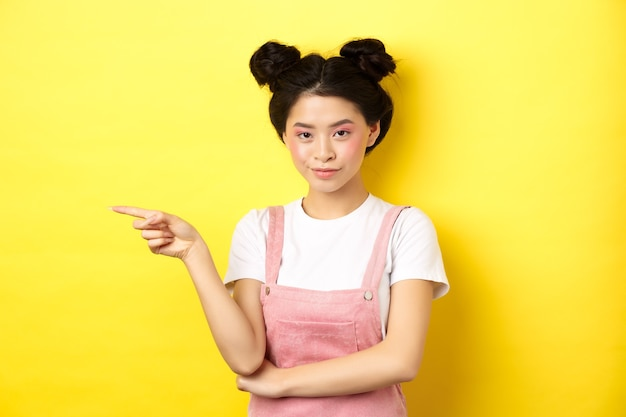Beautiful teenage asian girl with bright makeup, pointing finger left at banner and smiling, yellow.