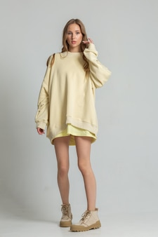白い背景の上のフルハイトポーズのカジュアルな服装で美しい10代の少女