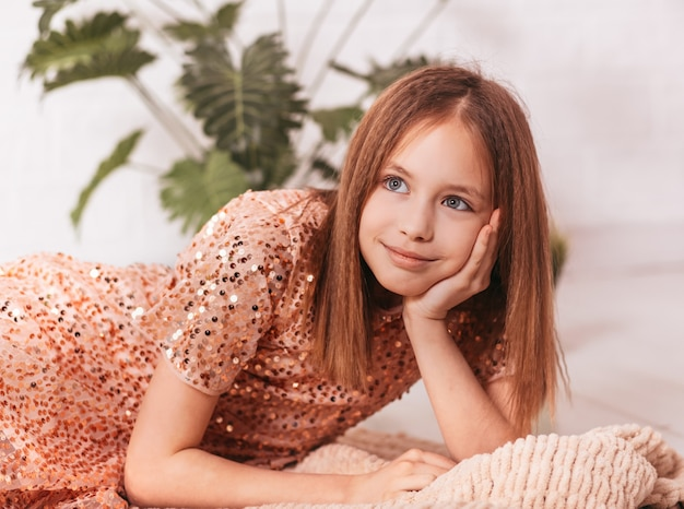 Красивая девочка-подросток в розовом платье лежит и мечтает в светлой комнате