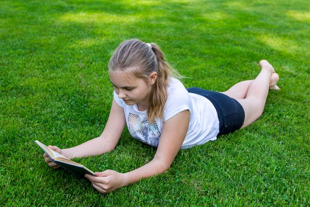 Beautiful teenage girl lies on grass and reads book in park on summer sunny day.