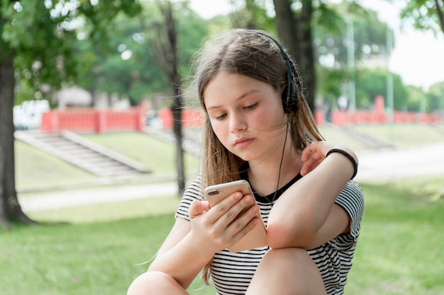 Beautiful teenage girl listening music while using cellphone at park