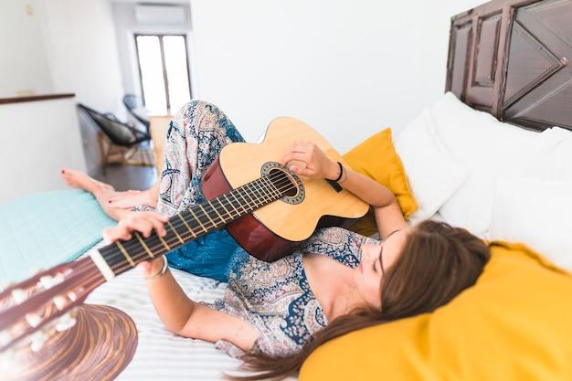 Beautiful teenage girl lying on bed playing guitar