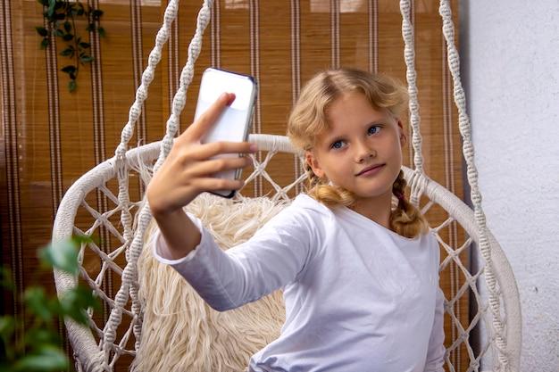 美しい十代の少女は、自宅で携帯電話でselfie