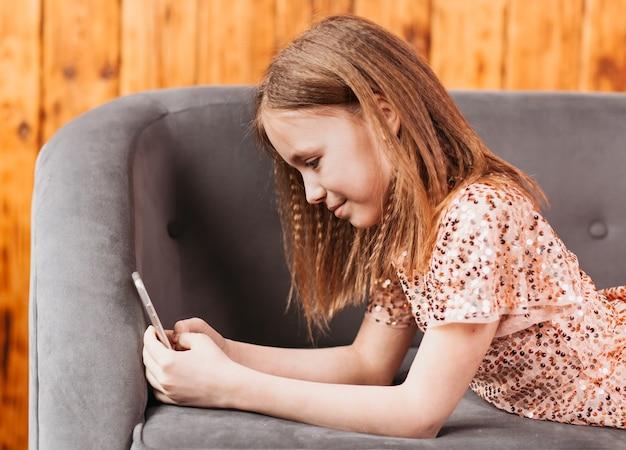 소파에 아름 다운 십 대 소녀는 소파에 누워 스마트 폰의 화면을 본다