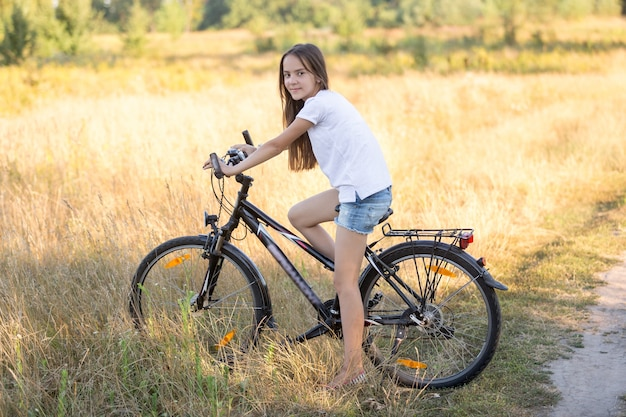 Beautiful teenage girl posing on bicycle in field at hot sunny day