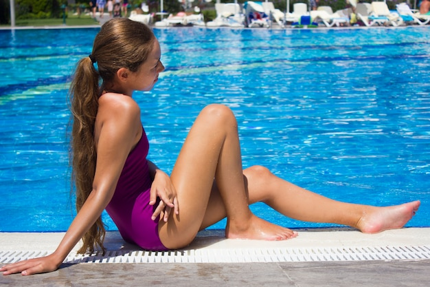 Beautiful teenage girl in purple swimsuit sitting by the poolside