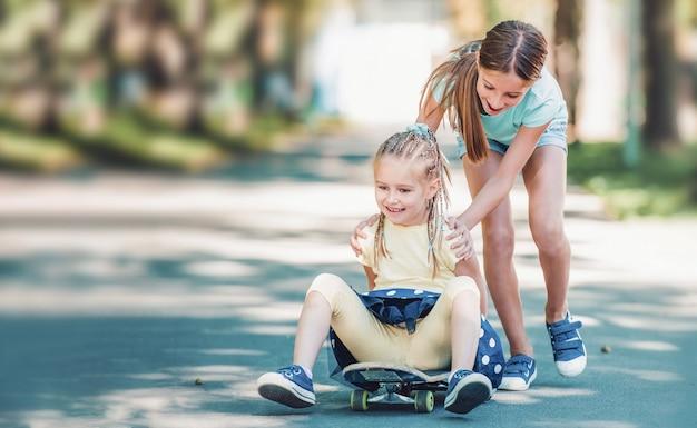 화창한 여름날 공원에서 스케이트보드를 타고 금발의 여동생을 타고 있는 아름다운 10대 소녀
