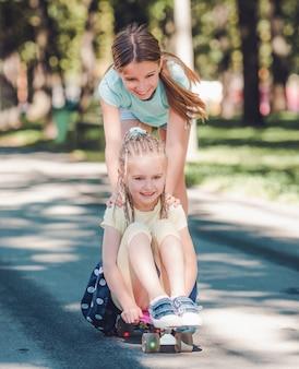 공원에서 스케이트보드를 탄 금발의 여동생을 타고 있는 아름다운 10대 소녀 프리미엄 사진