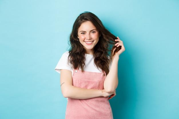Bella ragazza adolescente in attesa dell'estate, giocando con i capelli ricci e denti bianchi sorridenti, con fard carino e trucco glam sul viso, in piedi su sfondo blu