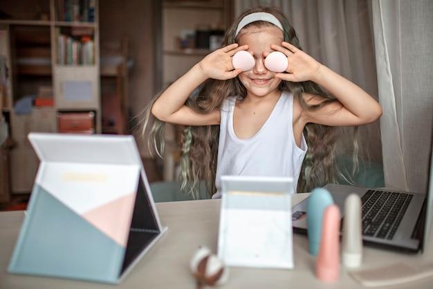 オンラインでタブレットで美容マスタークラスを見て、自分でスパの手順を実行している美しい10代の少女、顔に滑らかなマスクを持つ子供、自宅の美容院