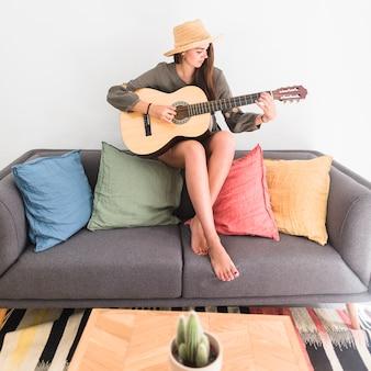 Beautiful teenage girl wearing hat sitting on sofa playing guitar