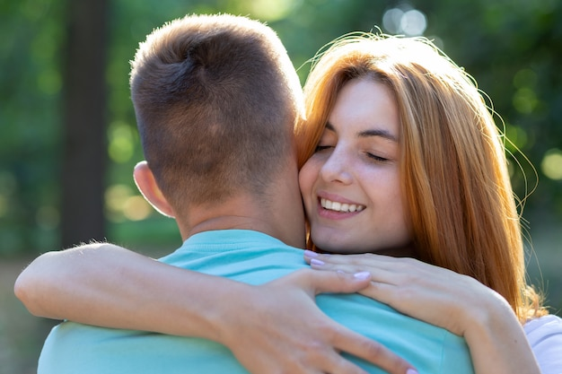 Beautiful teenage girl with bright red hair hugging her boyfriend outdoors. first love and romantic relationship .