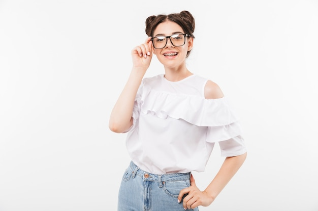 Beautiful teenage girl with double buns hairstyle and dental braces touching eyeglasses and smiling at camera in happy mood, isolated on white