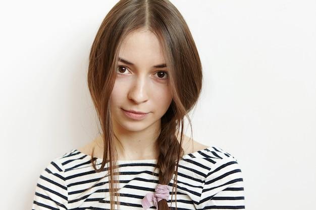 健康的な完璧な肌とスタジオの壁に対して隔離されるポーズ黒髪の美しい10代の少女