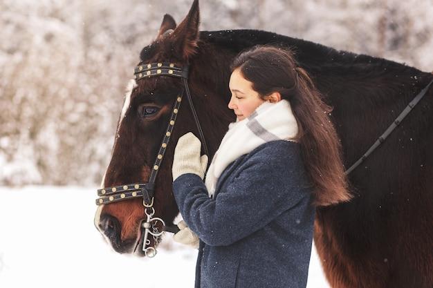公園で冬に長い髪のストローク茶色の馬を持つ美しい10代の少女