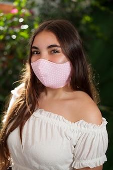 Красивая девочка-подросток с розовой маской для лица