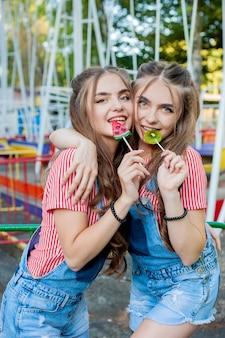 다채로운 박람회 명소에 막대 사탕 카라멜과 화려한 옷을 입고 아름다운 십대 쌍둥이 자매