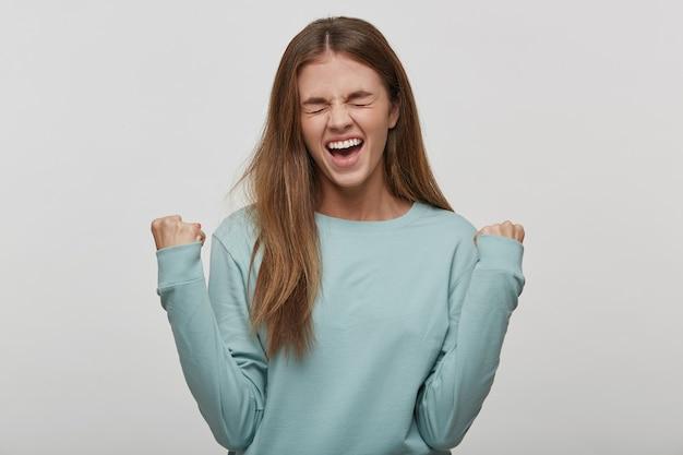 Красивая женщина-подросток счастлива и взволнована, выражая победный жест