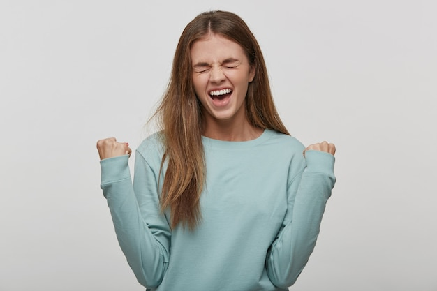 Beautiful teenage woman happy and excited expressing winning gesture