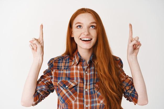 Bella donna adolescente con i capelli lunghi rossi, guardando e puntando le dita stupite, in piedi sul muro bianco