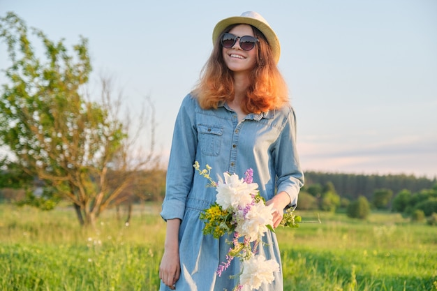Beautiful teenager in denim dress hat with bouquet of wildflowers
