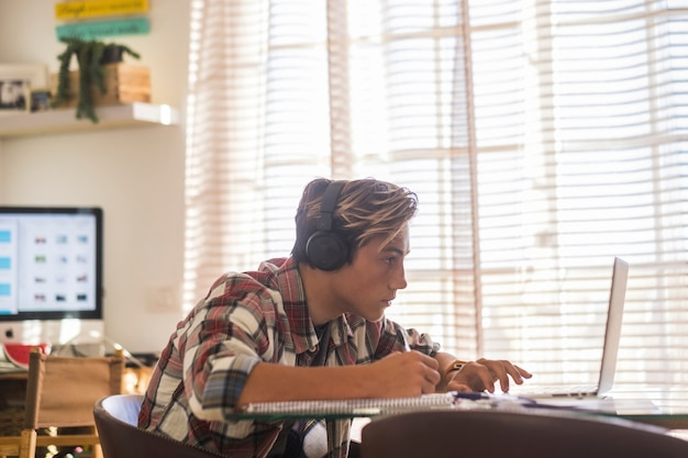 Beautiful teenager focus for his studies doing homework at home on the table with laptop or computer - headphones on the table - indor lifestyle concept - guy writing and reading