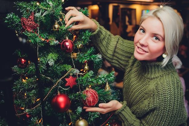 Красивая девушка-подросток украшает елку.