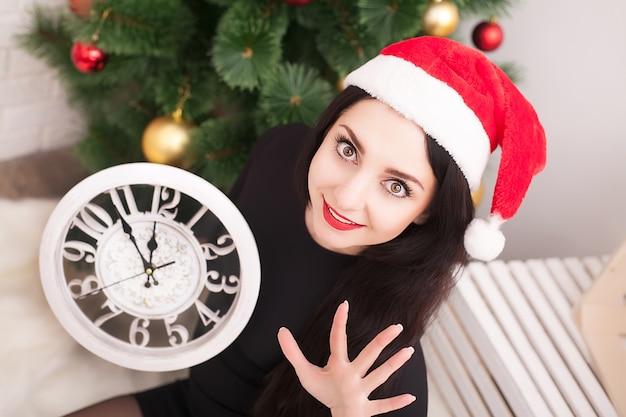 クリスマスツリーの隣の床に横たわっているサンタクロースの服を着た美しい10代の少女