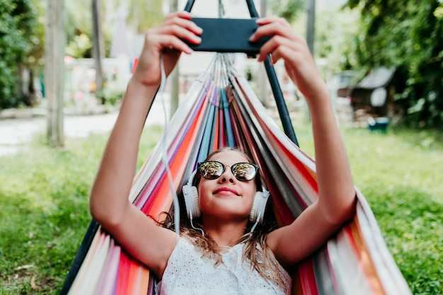 Beautiful teenager girl lying on colorful hammock at the garden. listening to music on mobile phone and headset and smiling
