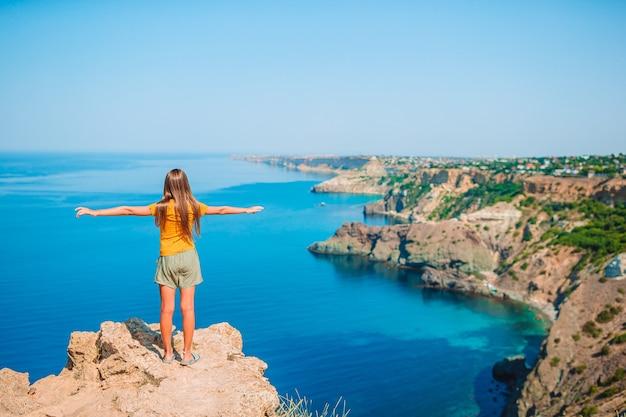 절벽의 가장자리에 아름다운 십 대 소녀는 산 정상 바위에보기를 즐길 수