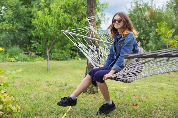 정원에서 해먹에서 쉬고 앉아 아름 다운 십 대 소녀