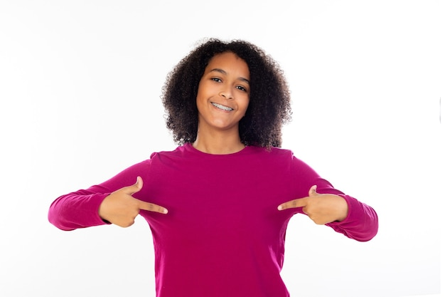 Beautiful teenager girl with pink sweater isolated on a white wall