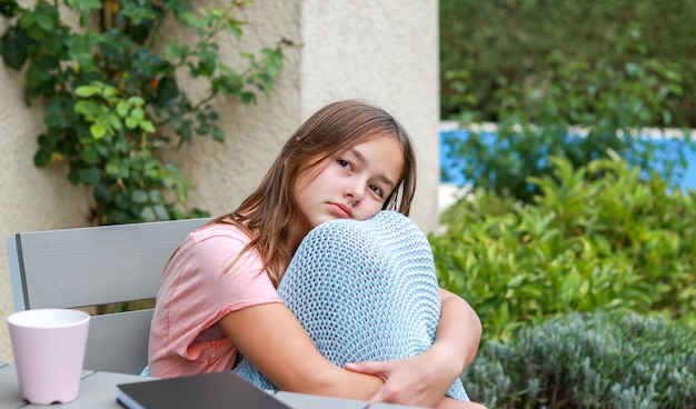 Beautiful teenager girl wrapped in warm knitted plaid daydreaming in garden hugging her kn