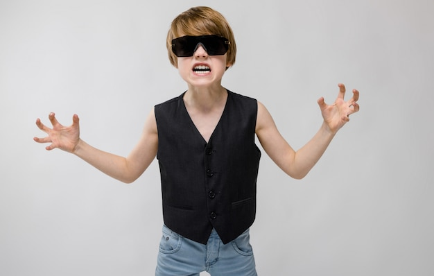 A beautiful teenager wearing black glasses, a black waistcoat and light jeans