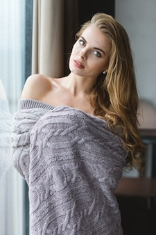 Beautiful tempting young woman with long hair standing near window in knitted coverlet