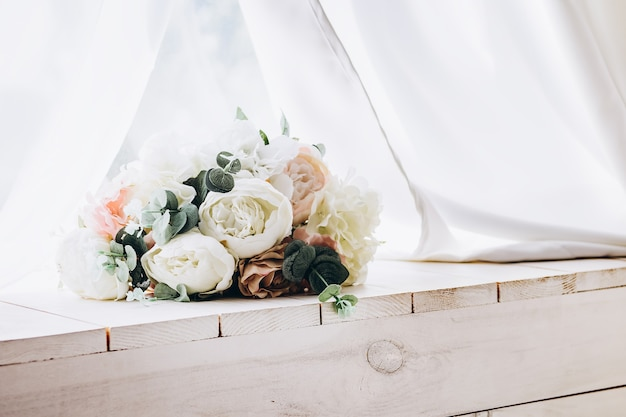 Beautiful tender bouquet of white flowers on wooden desk with white fabric on surface.