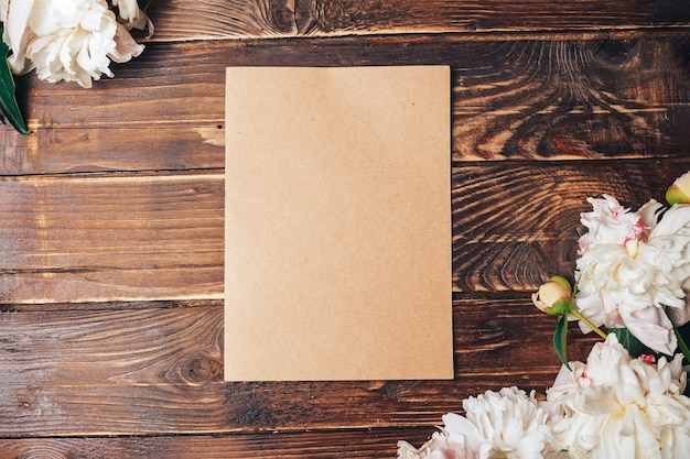 Beautiful tender peonies and a brown sheet of paper on a wood surface
