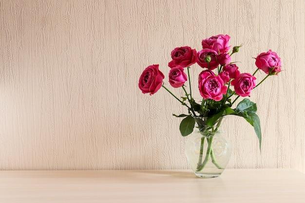 コピースペースとテーブルの上のガラスの花瓶の美しい柔らかいピンクのバラお祭りの花の背景