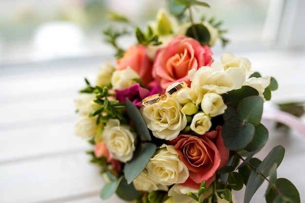 흐린 배경에 크림과 핑크 장미와 eustoma 꽃의 아름다운 부드러운 웨딩 부케