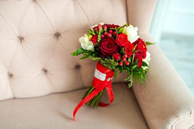 Красивый нежный свадебный букет из кремовых и красных роз цветов на фоне дивана цвета слоновой кости